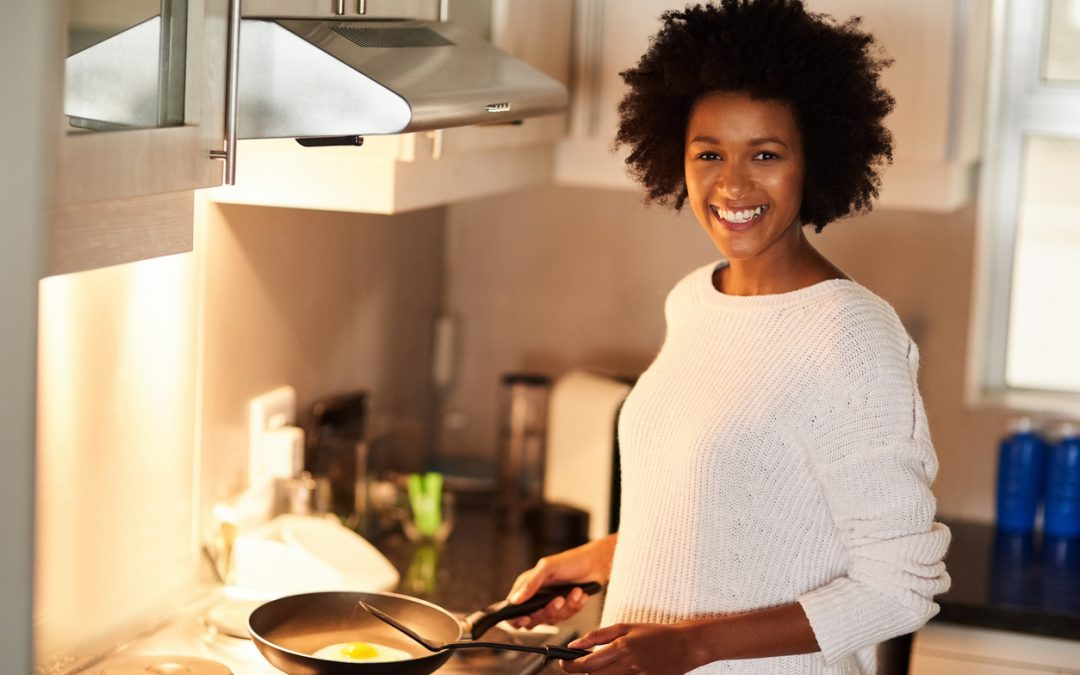 Shot of a happy young woman cooking a fried egg at home. paleo friendly egg recipes concept