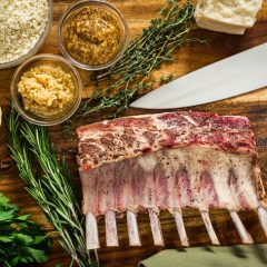 Cooking a roasted rack of lamb for dinner with a herbed parmesan cheese crust. Ingredients include rosemary, thyme, garlic, and mustard mixed with bread crumbs. All set on a cutting board with a chef knife.