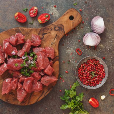 Fresh raw chopped angus beef on a wooden cutting board with spices, herbs and vegetables, stone background, top view