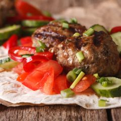 Turkish kofta with fresh vegetables on a flat bread close up on the table. horizontal