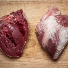 closeup photo of a whole and a cut lamb heart on a chopping board