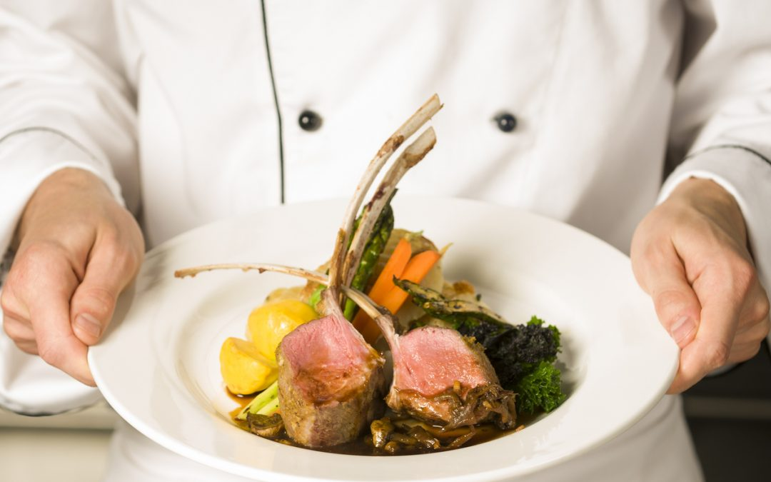 Chef holding a rack of grass-fed lamb entree
